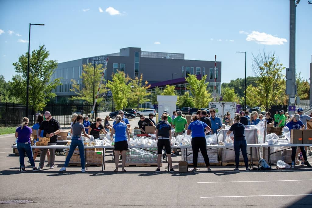 Polaris volunteers form assembly line to pack meal bags